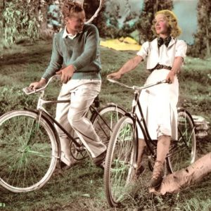 Tim Holt and Anne Shirley ride bikes.