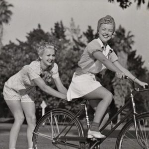 Phyllis Ruth rides a bike, Carole Landis skitches on skates.