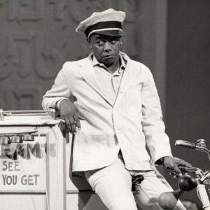 Flip Wilson rides an ice cream trike.