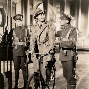 Brian Aherne rides a bike, stops to chat with British security.