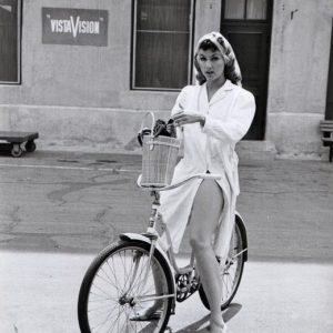 Julie Newmar rides a bike.
