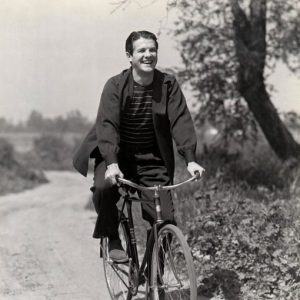 Robert Cummings rides a bike.