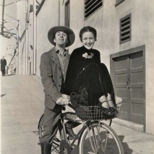 Ben Blue and Dorothy Lamour ride a bike.