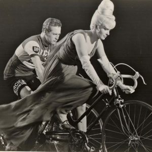 Joanne Woodward and Paul Newman ride bikes.