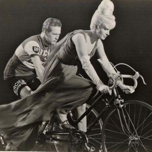 Joanne Woodward and Paul Newman ride bikes.