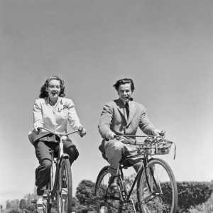 Evelyn Keyes and Glenn Ford ride bikes.
