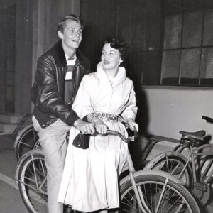 "Carleton Carpenter and Joan Evans ride a bike.Bicycle Not Built For Two – Joan Evans and Carleton Carpenter arrived at the ""Sunset Boulevard"" studio preview on Carleton's bicycle. They are quite a steady twosome. – Movie Stars Parade, 1950"