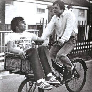 Christopher Timothy and Barry Evans ride a bike, 'round the mulberry bush.