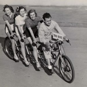 Rosemary, Lola and Priscilla Lane ride a taxi bike.