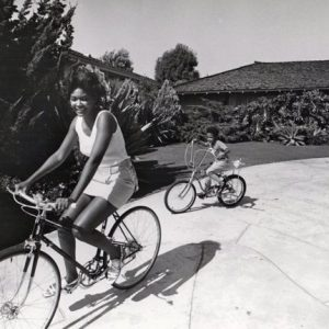 Mary Wilson and Pedro Antonio Jr. ride bikes.