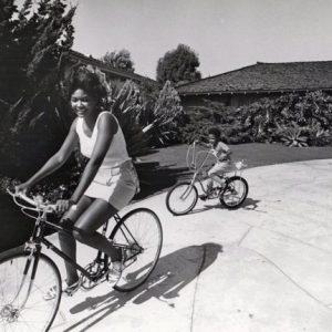 Mary Wilson and Pedro Antonio Jr. ride bikes.