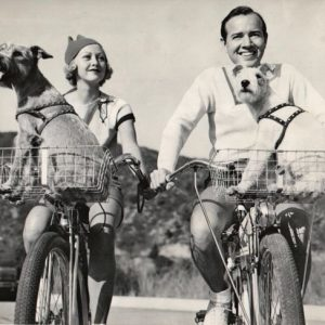 Evelyn Knapp and Earl Blackwell – and terriers – ride bikes.
