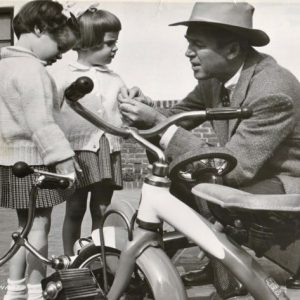 James Stewart does some quick tricycle repair work before twin daughters Judy and Kelly go for a ride.