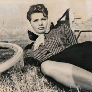 Sophia Loren rests by a bike.