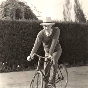 Walter Huston rides a bike.