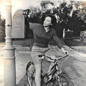 Leslie Caron rides a bike, mails a letter.