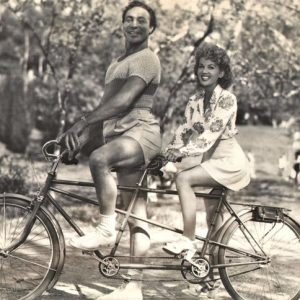 Max Baer and Marjorie Woodworth ride a bike.