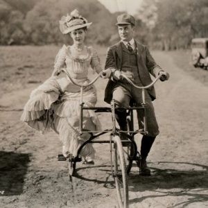 Patsy Ruth Miller and William Demarest ride a side-by-side trike.