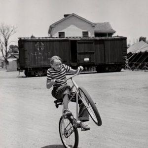 Claude Jarman Jr. wheelies a bike.