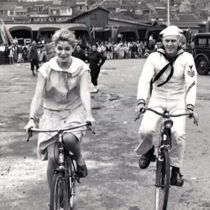Candice Bergen and Steve McQueen ride bikes.