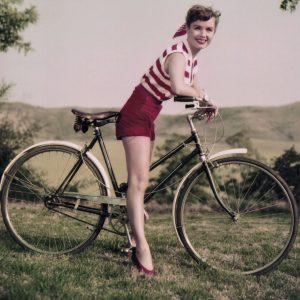 Debbie Reynolds rides a bike.