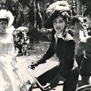 Gina Lollobrigida rides a bike.