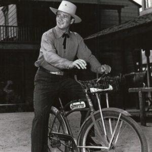 John Wayne rides a bike.