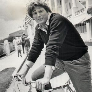 Christopher Reeve rides a bike.