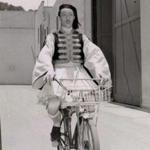 Mischa Auer rides a bike.