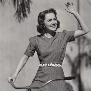 Olivia de Havilland rides a bike.