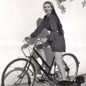 Patricia Morison rides a bike.