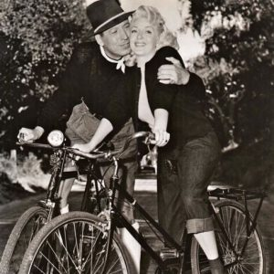 Barry Sullivan and Lana Turner ride bikes.