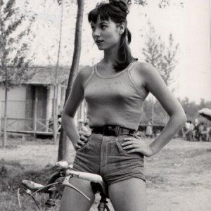Elsa Martinelli rides a bike.