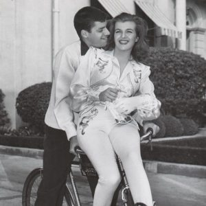 Jerry Lewis and Corinne Calvet ride a bike.