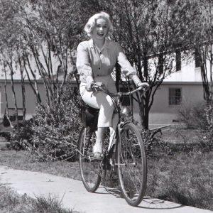 Mamie Van Doren rides a bike.