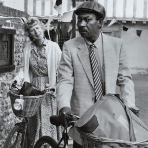 Helen Lindsay and Norman Beaton walk bikes.