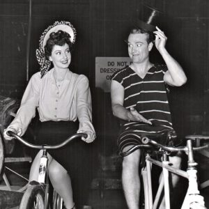 Virginia O'Brien and Red Skelton ride bikes.