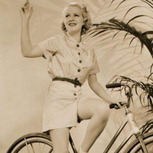 Claire Trevor rides a bike.