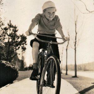Jackie Cooper rides a bike.