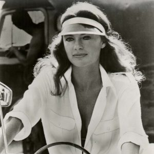 Jacqueline Bisset rides a bike.