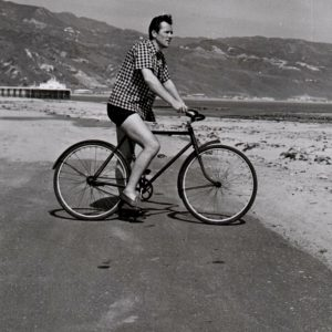 Howard Duff rides a bike.
