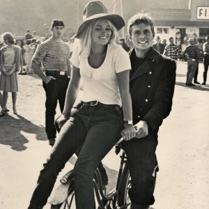 John Phillip Law and Andrea Dromm ride a bike.