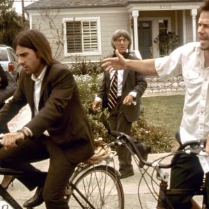 Jason Schwartzman and Mark Wahlberg ride bikes.