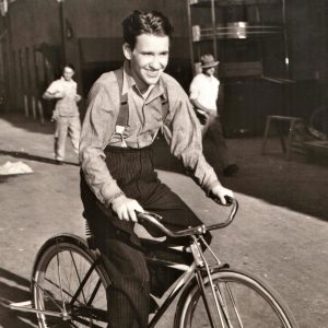 Burgess Meredith rides a bike.