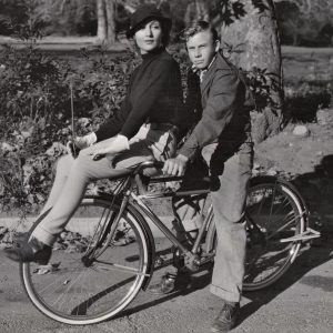 Carole Lombard and Donald Haines ride a bike.
