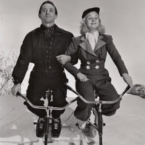 "Harry ""Heinie"" Cooper and June Preisser ride ski-bikes."