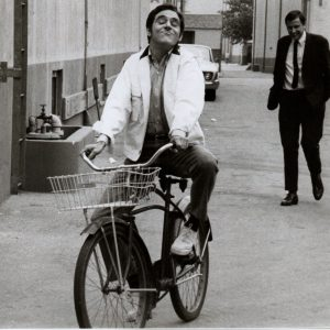 Anthony Newley rides a bike.