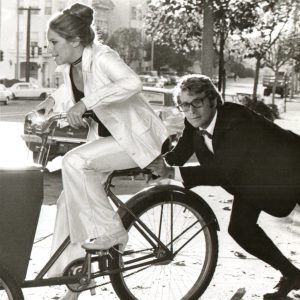 Barbra Streisand rides a bike, Ryan O'Neal gives a push.
