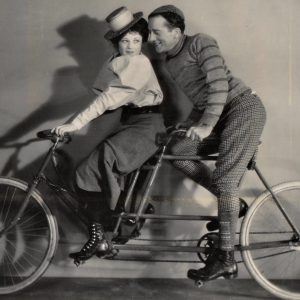 Sally Eilers and Jack Mulhall ride a bike.
