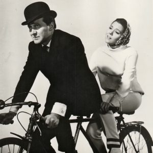 Patrick Macnee and Diana Rigg ride a bike.
